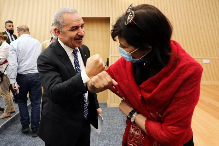De Palestijnse premier Mohammed Shtayyeh groet een journalist na de persconferentie waar hij zijn voornemens aankondigde. Beeld AP
