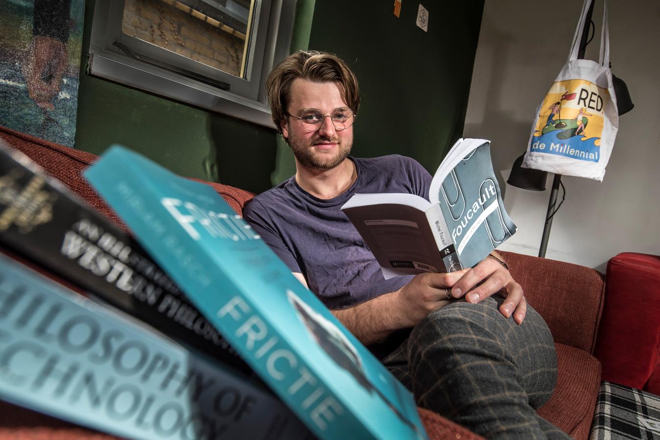 """Bouke van Dalen, filosofiestudent, thuis op de bank. """"Als je het digitaal volgt, blijft het oppervlakkig. Met een studie als filosofie is dat funest. Je moet in die ruimte zijn om juist die kleine menselijke interacties aan te voelen en aan te gaan."""""""