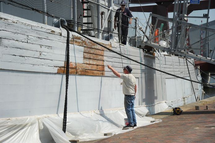 Vrijwilliger Herman Woltering bezig met het verven van de romp van museumschip Mercuur, dat aan de Houtkade ligt.
