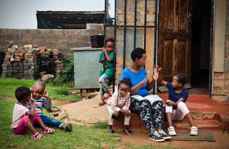 Tebogo Moloto neemt met haar dochter Bonolo rekenopdrachten door op de stoep voor hun huis.  Beeld Bram Lammers
