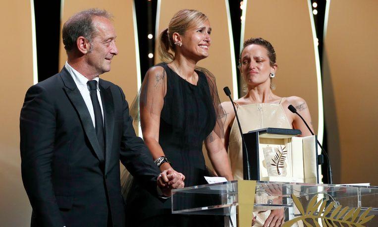 Regisseur Julia Ducournau (midden) neemt de Gouden Palm in ontvangst. Naast haar Titane-acteurs Vincent Lindon en Agathe Rousselle (rechts).  Beeld REUTERS
