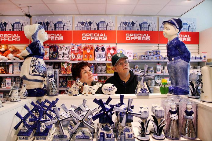 Amerikaanse toeristen vergapen zich aan het Delfts Blauw in een winkel op de Markt in Delft.