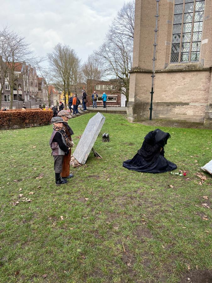 Lady Dedlock is incognito op zoek naar het graf van Nemo op de begraafplaats naast de Bergkerk. Om haar heen loopt het publiek op afstand.