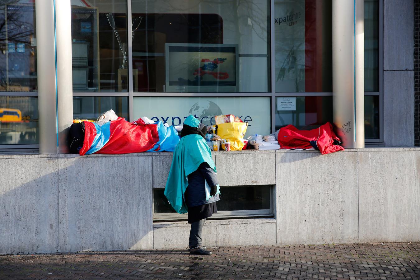 Een dakloze houdt de wacht bij zijn spullen.