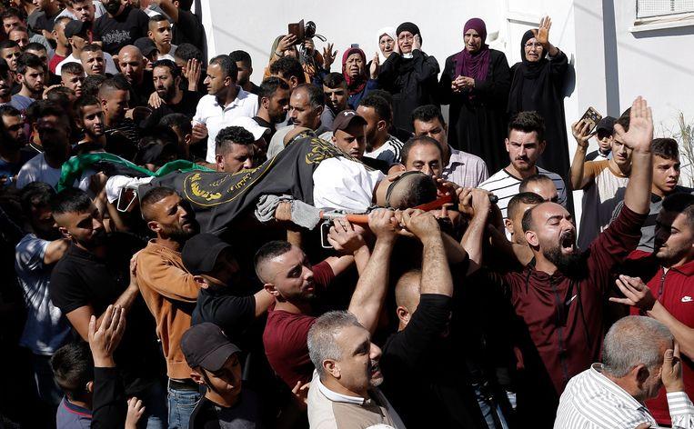 Rouwende Palestijnen dragen het lichaam van de 22-jarige Osama Sobh, zondag gedood tijdens een Israëlische nachtelijke militaire inval.  Beeld EPA