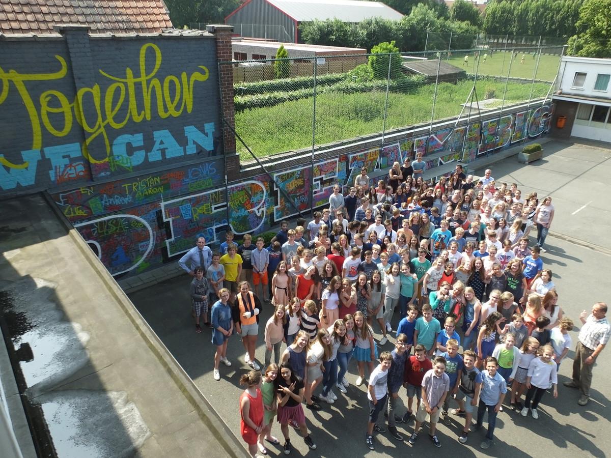 De eerstejaars van Leiepoort campus Sint-Hendrik bij de muur op de speelplaats. Daarop prijkt de slogan 'Together we can dream big'.