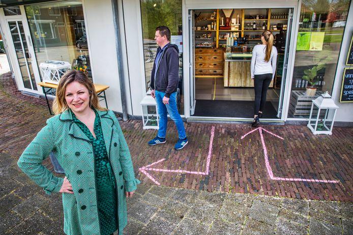 Danica Mast (links) doet onderzoek naar visuele aanwijzingen in verband met de coronamaatregelen. Hier staat ze bij de winkel Jimmie's waar ze met krijt hebben aangegeven hoe je de winkel in en uit moet gaan zonder elkaar voor de voeten te lopen. (Den Haag 14-04-20) Foto: Frank Jansen.
