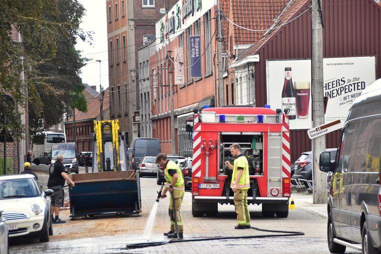 De brandweer spoelt de moutresten van het wegdek in de Spanjestraat.