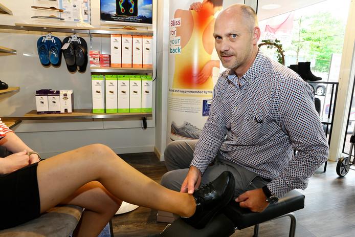 """Herman Quist van Quist Schoenen & Outdoor helpt een klant aan een nieuw paar schoenen. ,,Wij investeren veel in de klant. Ze staan hier niet binnen tien minuten buiten."""""""