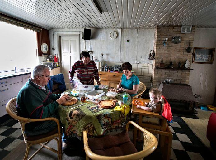 Wim en Dymph Claes eten en koken nog in hun voormalige woning in Luyksgestel. Dochter Elly en kleindochter Petra prikken een vorkje mee.