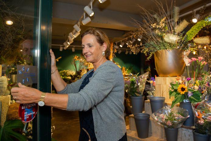 Tilly Kouwenberg van Karakter Bloemen plakt de sticker met het Zilveren Keurmerk van Ongehinderd op de deur.