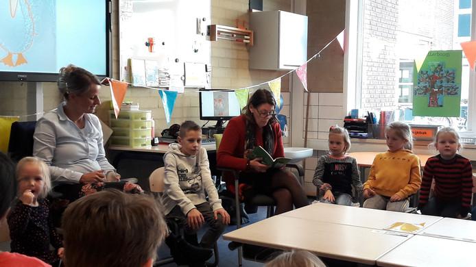 Burgemeester José van Egmond (met geleende leesbril) leest voor uit het boek van Ingrid van den Broek (links). De groep 3/4-kinderen van De Parelmoer in Yerseke luisteren aandachtig.