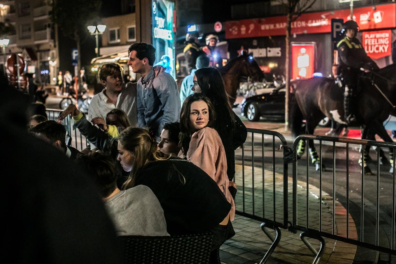 Agenten te paard patrouilleren in Knokke, terwijl de jeugd feestviert. Beeld Bas Bogaerts