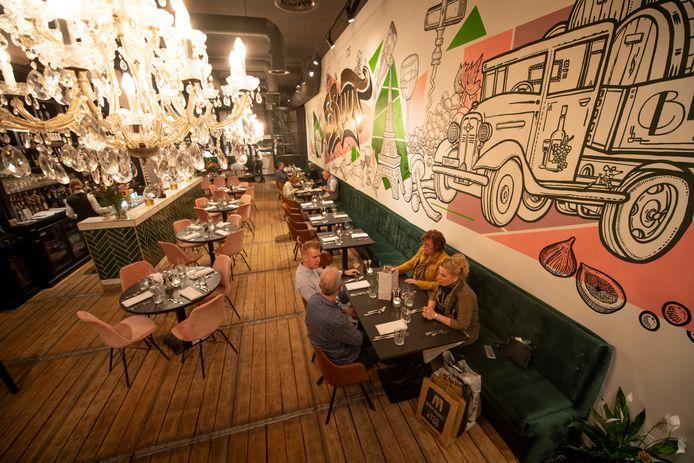 De bistro is een sfeervol ingerichte, opvallend hoge ruimte. Achterin is de keukenbrigade aan het werk te zien