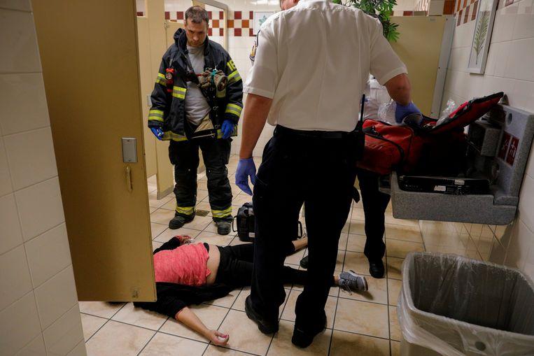 Ambulancemedewerkers zijn toegesneld om deze 40-jarige vrouw te reanimeren, die in het toilet van een winkel een overdosis pijnstillers heeft ingenomen.  Beeld Reuters