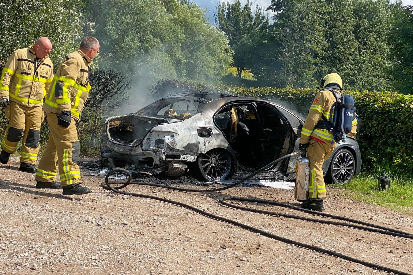 De brandweer in actie bij de volkomen uitgebrande auto.