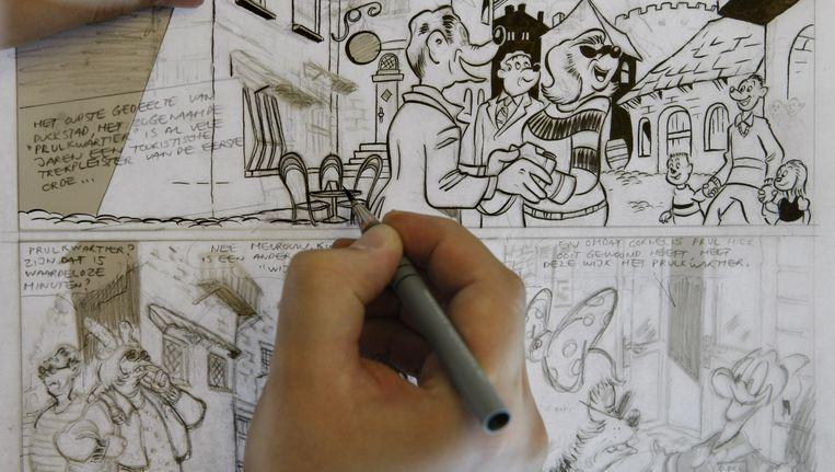 Een inkter werkt aan een strip op de redactie van Donald Duck in Hoofddorp. Beeld anp