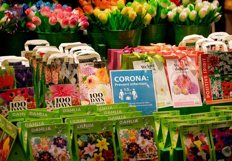 Een waarschuwingsbordje voor het coronavirus op Schiphol. Beeld ANP