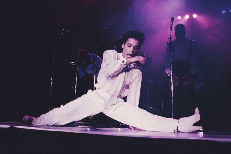 Prince, met kenmerkende hoge hakken, maakt een split op het podium van de Wembley Arena in Londen, in 1986. Beeld Getty Images