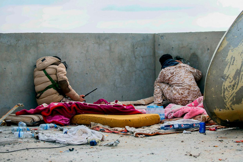 Twee regeringsgezinde strijders spieden door een muur in een buitenwijk van de Libische hoofdstad Tripoli. Beeld AFP