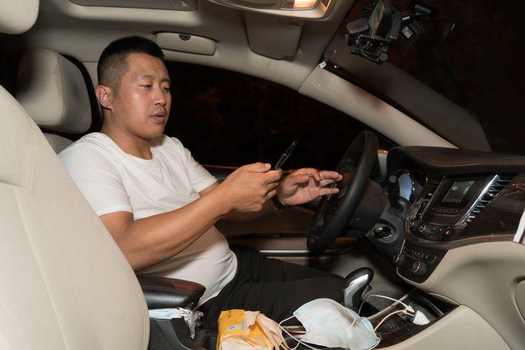 Miao Zhiwen maakt diensten van vijftien uur voor het taxiplatform Didi. Beeld Ruben Lundgren
