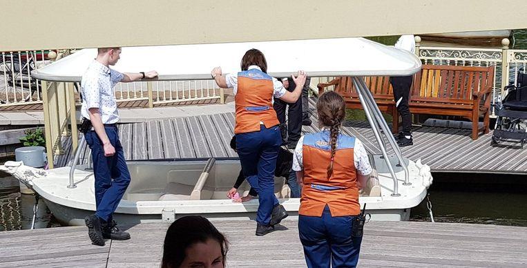 Onder toeziend oog van het personeel ruimen de jongeren de rotzooi in het bootje op.