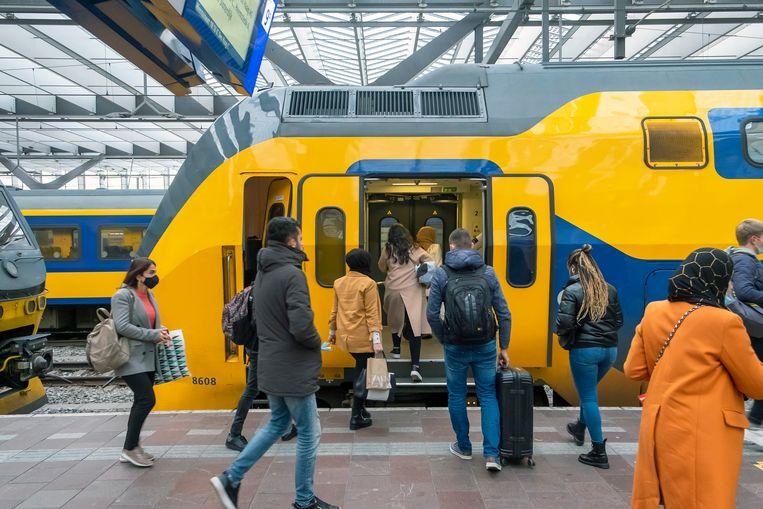 Passagiers met mondkapjes op stappen in een trein op Rotterdam CS. Beeld Hollandse Hoogte / Hans van Rhoon