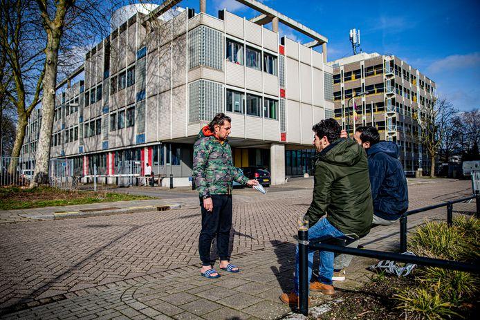 Lewaa Alnassani in gesprek met medebewoners, achter hem het opvangcomplex. Kantoorruimtes die misschien al te verouderd zijn om in te werken, laat staan geschikt om lange tijd in te wonen.