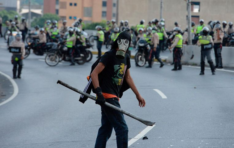 TOPSHOT - A Venezuelan opposition activist clashes with police forces during a demonstration against President Nicolas Maduro in Caracas, on April 24, 2017. Protesters rallied on Monday vowing to block Venezuela's main roads to raise pressure on Maduro after three weeks of deadly unrest that have left 21 people dead. Riot police fired rubber bullets and tear gas to break up one of the first rallies in eastern Caracas early Monday while other groups were gathering elsewhere, the opposition said.  / AFP PHOTO / Federico PARRA Beeld afp
