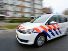 Druk bellende scooteraar rijdt door rood terwijl de politie staat te wachten