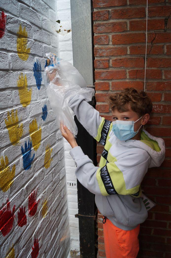 Deze jongeman zet zijn handtekening op de muur