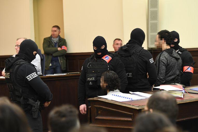 Salah Abdeslam (zittend in het midden) en Sofien Ayari (rechts). Beeld BELGA