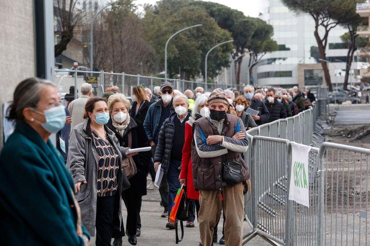 Mensen schuiven aan bij een vaccinatiecentrum in Rome. Beeld EPA