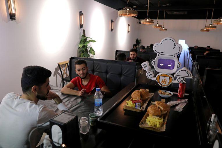 """""""En de hamburger is voor ...?"""" Een robot serveert in een restaurant in Kerbala in Irak.  Zo kan iedereen anderhalve meter afstand houden.  Beeld Abdullah Dhiaa al-Deen, REUTERS"""