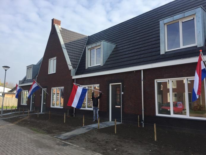 Een van de bewoners van de nieuwe woningen hangt de vlag uit.