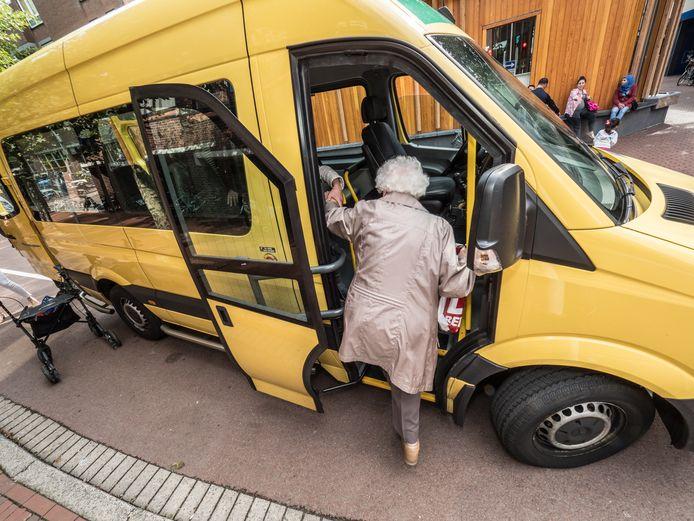 Een dame op leeftijd stapt in de Ouderenbus, die weer gaat rijden.
