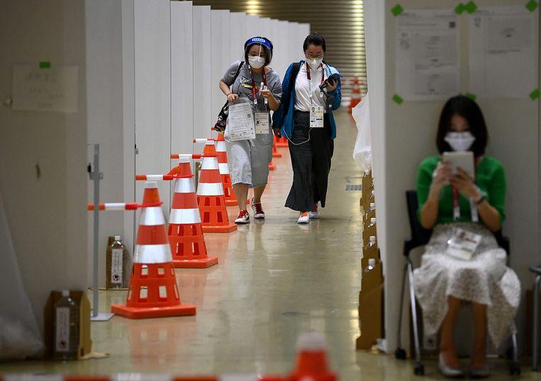 Journalisten leveren in aanloop naar het begin van de Olympische Spelen in Tokio dagelijkse speekseltesten in.  Beeld AFP