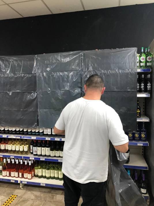 De wijnflessen verdwijnen achter uit plastic zakken bij de avondwinkel aan de Hommelstraat in Arnhem, kort nadat burgemeester Marcouch officieel het verbod op de verkoop van alcoholhoudende drank na 22.00 uur bekend maakte.