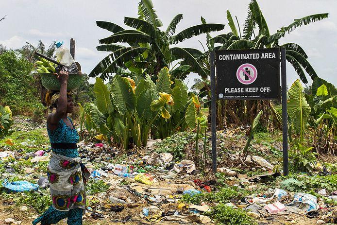 Een Nigeriaanse vrouw wandelt voorbij een bord dat waarschuwt voor vervuilde grond.