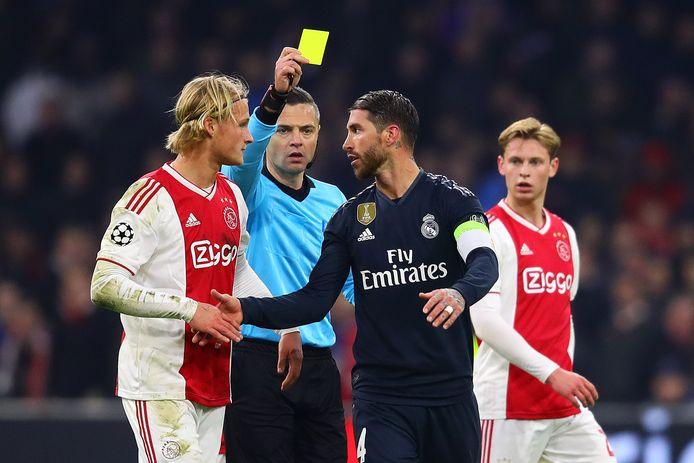 Arbiter Damir Skomina houdt Sergio Ramos de gele kaart voor na een overtreding op Kasper Dolberg (links).