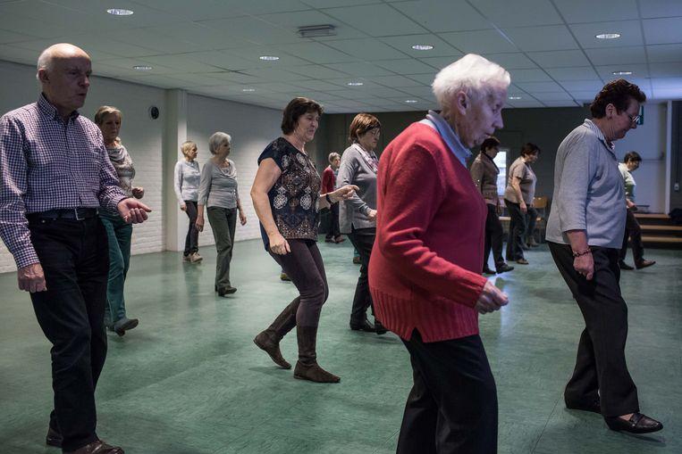 De mensen van Okra, de ouderenorganisatie van de christelijke mutualiteiten, tijdens het wekelijks uurtje lijndans in de bib van Edegem.  Beeld Bas Bogaerts