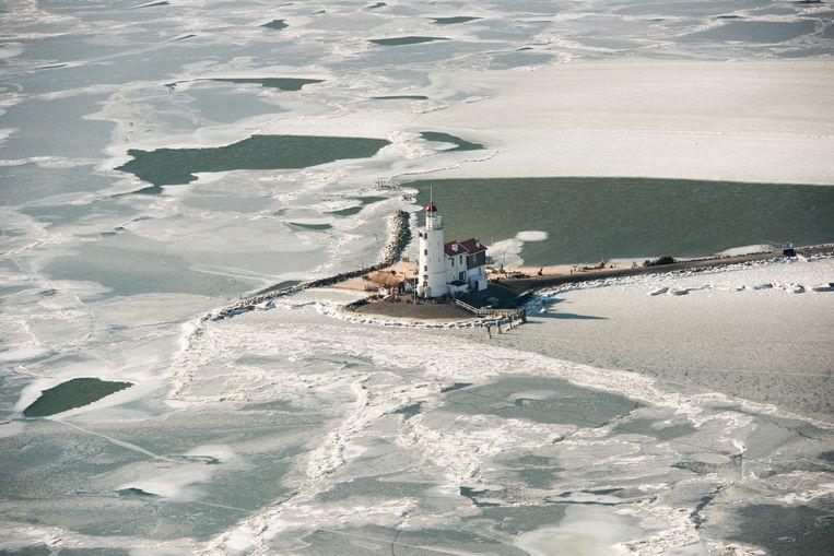 De vuurtoren Het Paard van Marken aan het Markermeer dat gedeeltelijk bedekt is met ijs.  Beeld ANP