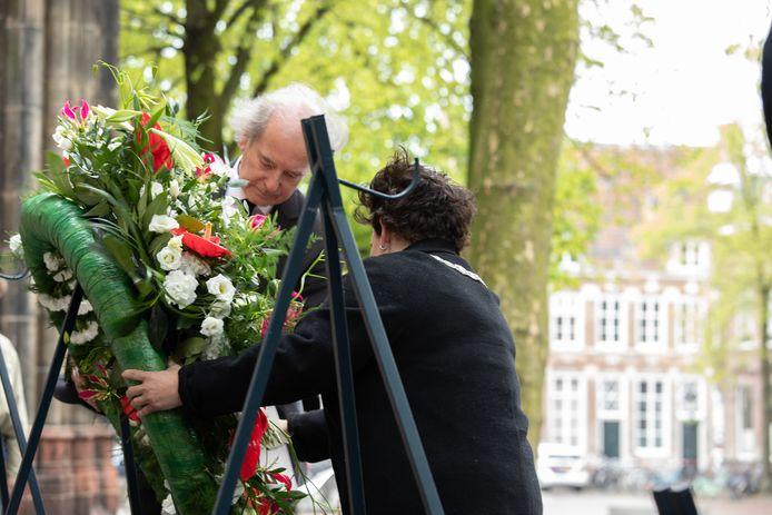 Burgemeester Dijksma en Klaas Taselaar leggen een krans bij het Verzetsmonument op het Domplein in Utrecht.