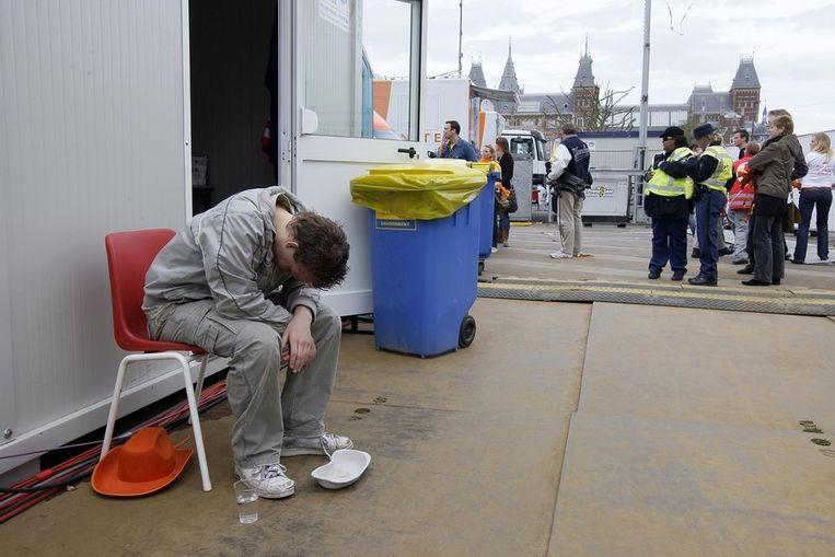 Een feestganger zit bij te komen op de Eerste Hulppost op het Museumplein tijdens Koninginnedag in Amsterdam. Beeld ANP