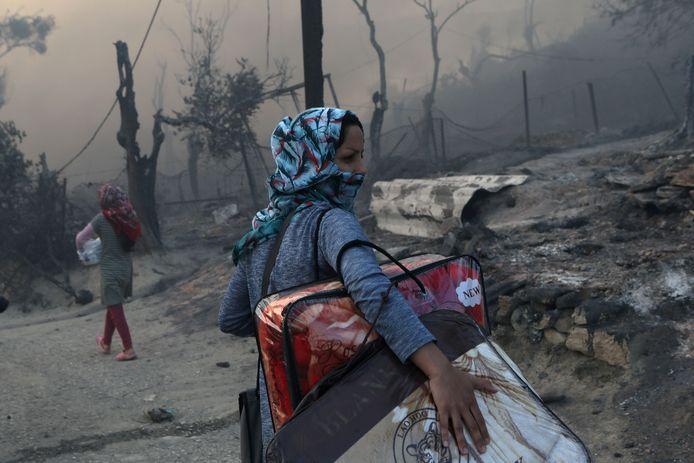 Een vrouw draagt haar bezittingen weg uit het afgebrande kamp Moria op Lesbos. Archiefbeeld.