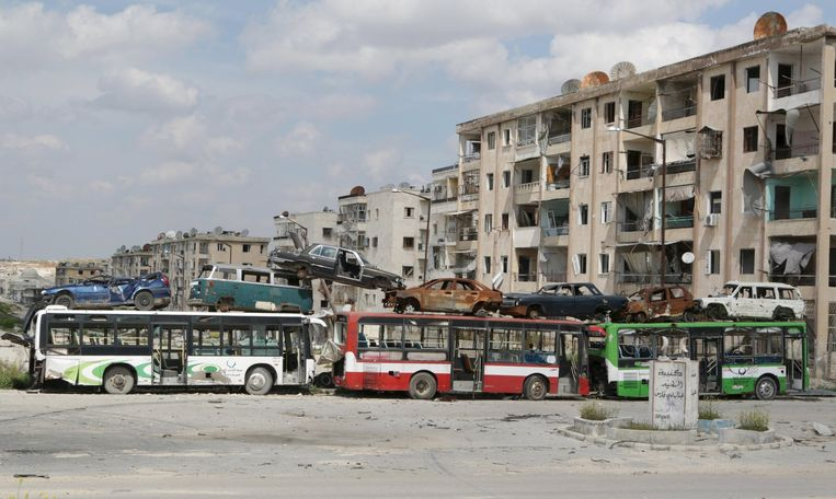 Een geïmproviseerde muur van bussen en wrakstukken van auto's in Aleppo, april 2015. Beeld reuters