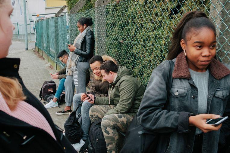 Leerlingen van Don Bosco Groot-Bijgaarden wachten op de bus en kijken op hun smartphone. Beeld Illias Teirlinck