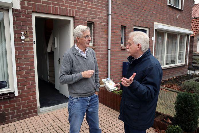 Wethouder Henk Wessel (rechts) deelt zakjes bloembollen uit na de aanleg van het wateropvangsysteem in 't Harde. (archieffoto)