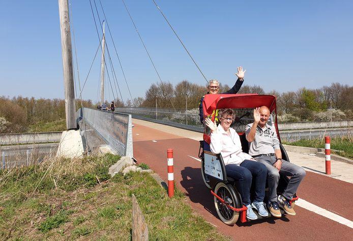 Vrijwilliger met twee klanten in de riksja, rijd over de fietsbrug over de A28