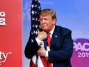 Donald Trump omarmt de Amerikaanse vlag bij het betreden van het podium van de CPAC in 2019 in National Harbor, Maryland. De conferentie van de conservatieve omgeving is voor hem een vertrouwde omgeving en in 2021 de 'perfecte plek' voor zijn terugkeer op het podium van de Amerikaanse politiek, aldus zijn adviseurs. (Foto NICHOLAS KAMM / AFP)